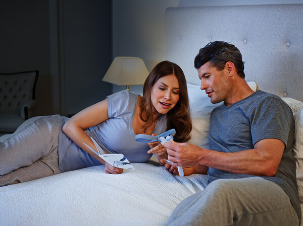woman and man on bed before sleep apnea therapy cycle.